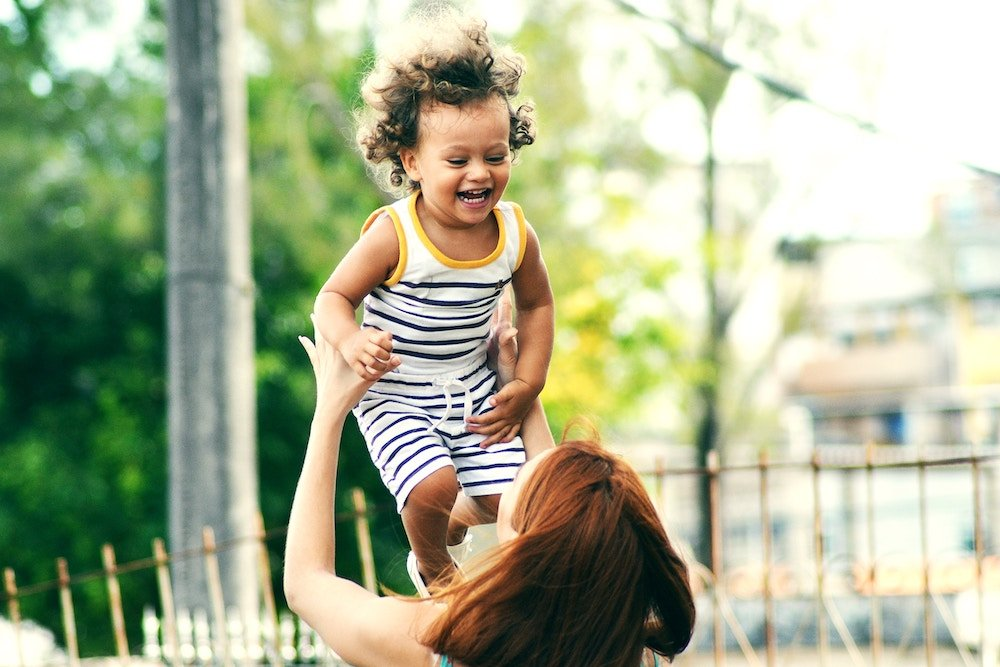 Mom throwing happy smiling kid in the air