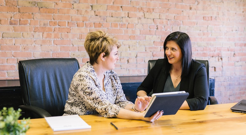 Two women discussing teen entrepreneur class for kids